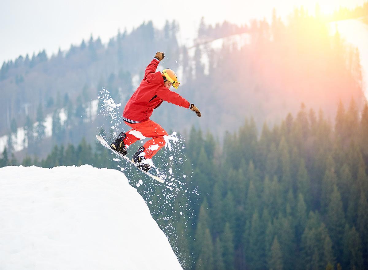 человек прыгает на сноуборде